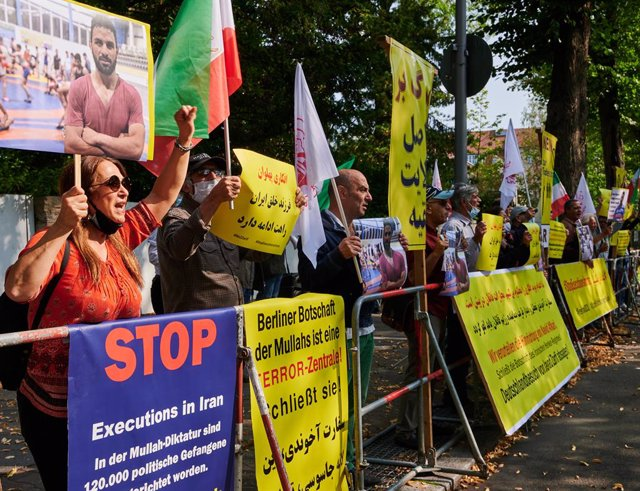 12 September 2020, Berlin: People take part in a protest in front of the Iranian embassy against the execution of Iranian wrestler Navid Afkari over the murder of a security guard during anti-government protests in 2018. Photo: Annette Riedl/dpa