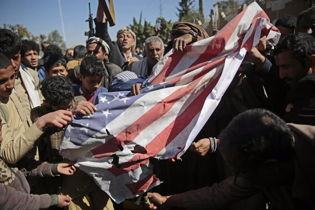 18 January 2021, Yemen, Sanaa: Houthi supporters burn a US flag during a protest in front of the US embassy in Sanaa against the United States over its decision to designate the Houthi rebels movement as a foreign terrorist organization. Photo: Hani Al-An