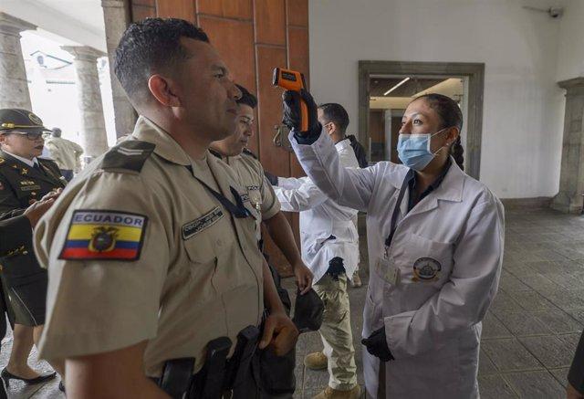 Personal médico comprueba la temperatura de varios agentes de la Policía de Ecuador, en medio de la crisis sanitaria de la COVID-19.