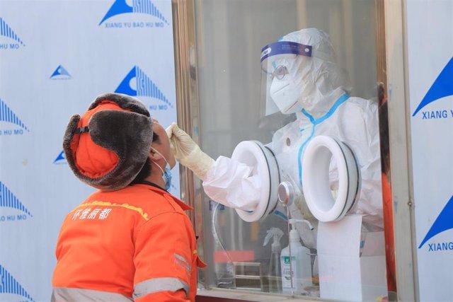 Personal médico realiza una prueba de coronavirus en un centro médico de Pekín, Perú.