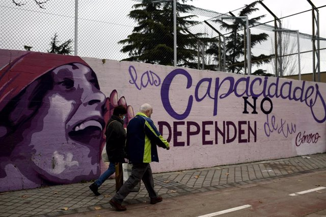 Dos personas pasan por el mural feminista en el polideportivo municipal de la Concepción en el distrito de Ciudad Lineal