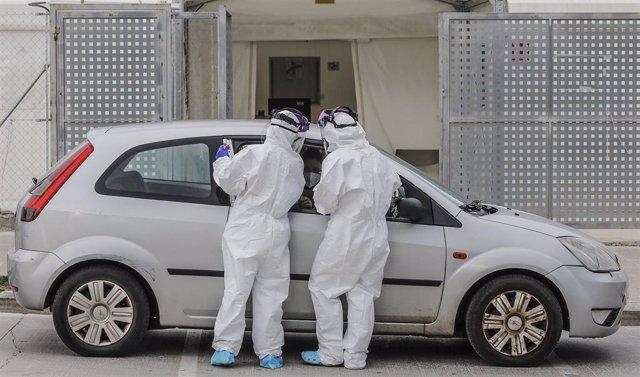 Dos sanitarios realizan una prueba PCR a una persona desde su vehículo en una imagen de archivo.