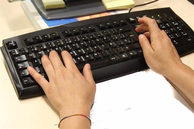 Un trabajador escribiendo en un teclado de ordenador.