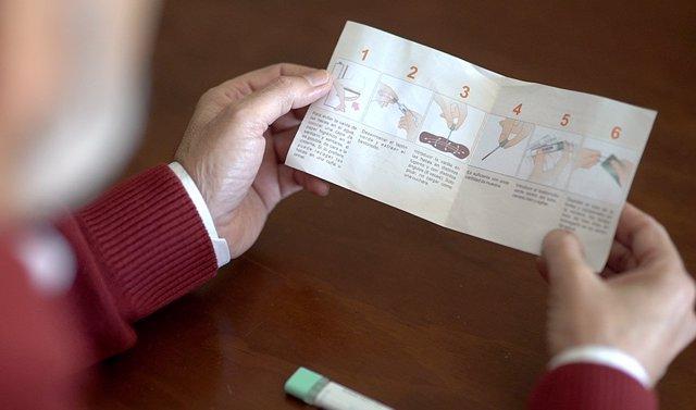 Un hombre lee el folleto con la información sobre el cribado del cáncer de colon