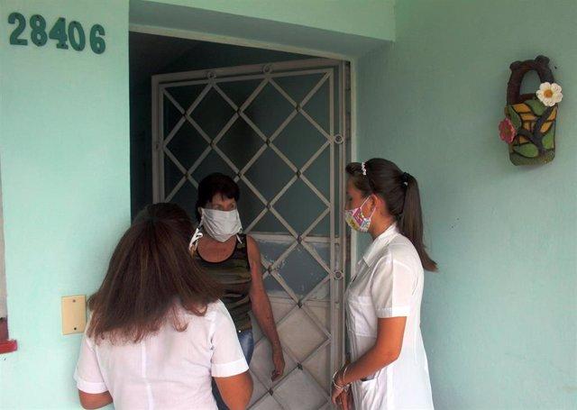 Estudiantes de medicina cubanos preguntan a una mujer en La Habana sobre posibles síntomas de covid-19