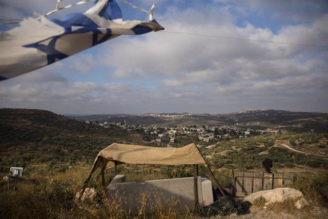 Un soldado israelí observa la aldea palestina de Kfar Kadum mientras custodia el asentamiento judío de Har Hemed cerca de Nablus, en Har Hemed, Cisjordania.
