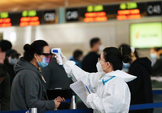Toma de temperatura a una mujer en el aeropuerto de Los Angeles.