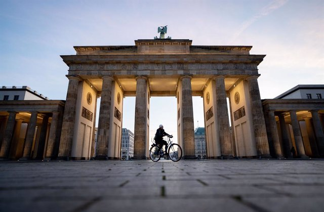 17 December 2020, Berlin: A woman rides his bicycle across the empty March 18 Square at the Brandenburg Gate amid a nationwide lockdown that came into force on Wednesday to tackle the surging numbers of new coronavirus cases. Photo: Kay Nietfeld/dpa