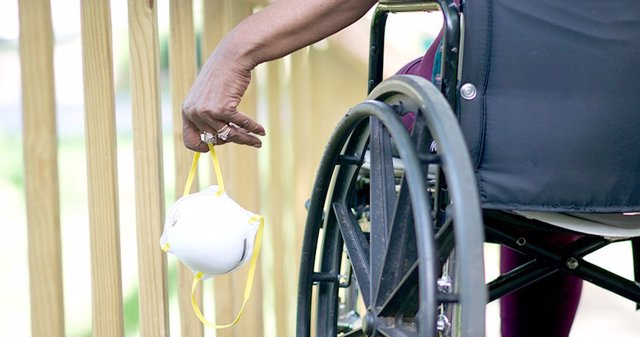 Persona en sillas de ruedas portando mascarilla.