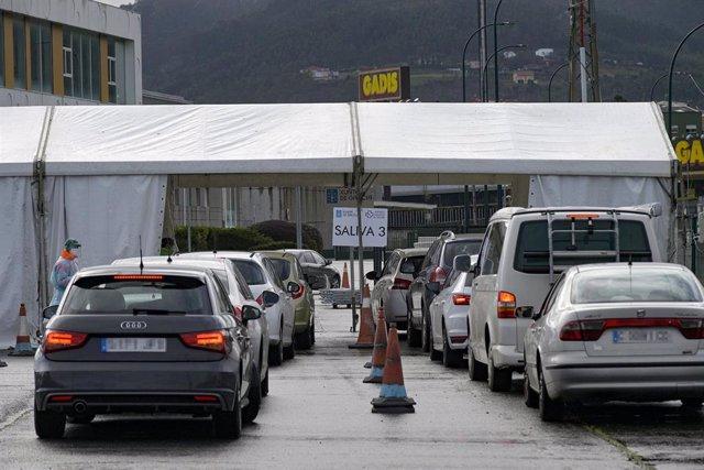 Filas de coches para recoger el test de saliva en la Avenida de Arsenio Iglesias en Arteixo, A Coruña.