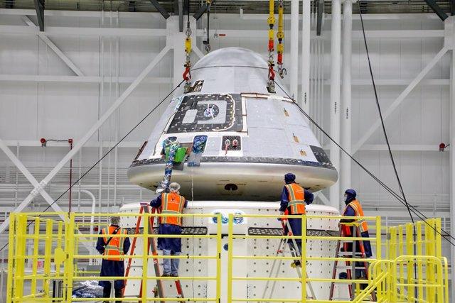 Los técnicos observan que el módulo de tripulación Starliner de Boeing se coloca encima del módulo de servicio en la instalación de procesamiento de carga y tripulación comercial en el Centro Espacial Kennedy de la NASA en Florida el 14 de Enero de 2021