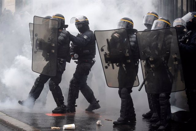 16 January 2021, France, Nantes: Smoke from tear gas bombs surrounds anti-riot police officers during a protest against the global security draft law that would restrict publication of pictures showing the faces of police officers on duty. Photo: Sebastie