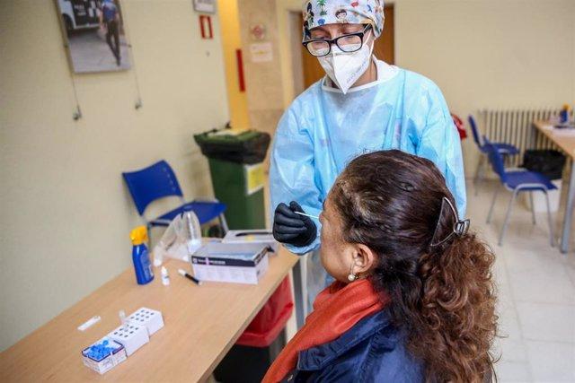 Una sanitaria realiza un test de antígenos a una mujer.