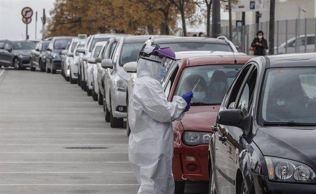Un sanitario realiza una prueba PCR a una persona desde su vehículo para la detección del coronavirus.