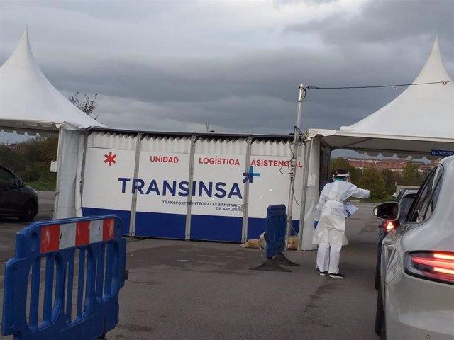 Carpa de Transinsa en la que se ha instalado un Autocovid en Gijón, con coches esperando a la realización de las PCR.