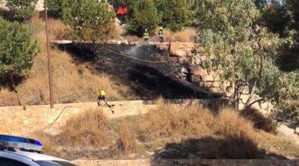 Los Bomberos extinguen un incendio forestal en la ladera del castillo San Fernando de Alicante