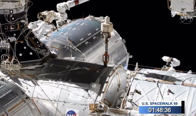 Dos astronautas trabajan en el exterior de la Estación Espacial sujetos al brazo robótico