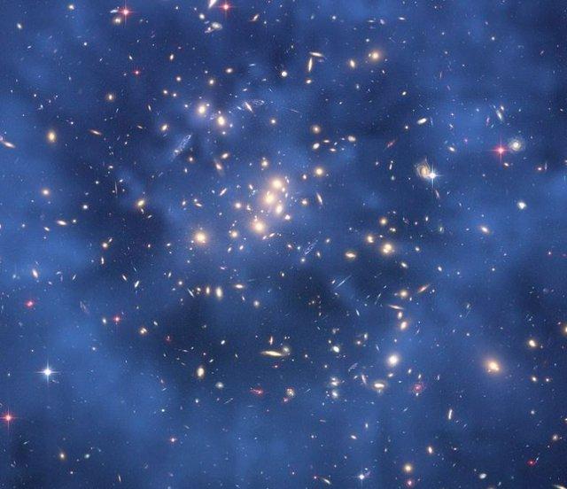 Imagen compuesta del cúmulo de galaxias CL0024+17 tomada por el telescopio espacial Hubble que muestra la creación de un efecto de lente gravitacional. Se supone que este efecto se debe, en gran parte, a la interacción gravitatoria con la materia oscura.