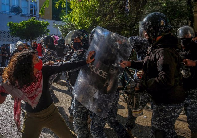 29 December 2020, Lebanon, Beirut: Riot policemen clash with university students and anti-government activists during a demonstration against high tuition fees amid the ongoing economic crisis and political impasse, outside the American University in Beir