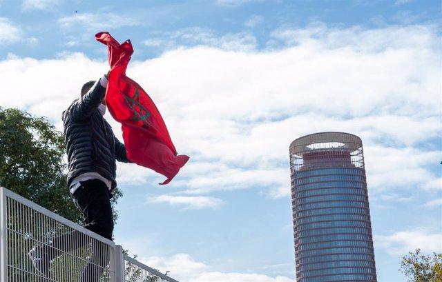 Un ciudadano dentro del consulado de Marrueco, mostrando la bandera de Marruecos en la manifestantes de la Liga de Estudiantes y Jóvenes Saharauis en el Estado Español en la concentración junto a la embajada de Marruecos para apoyar al pueblo saharaui. Se