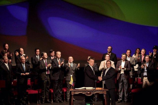 El expresidente de Colombia Juan Manuel Santos y Rodrigo Londoño, junto al resto del alta mando de las extintas FARC en la firma de los acuerdos de paz de 2016.