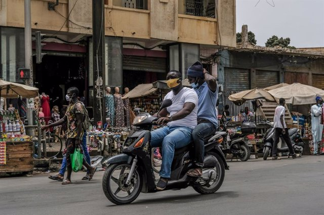 Dos hombres con mascarilla en una moto en Dakar