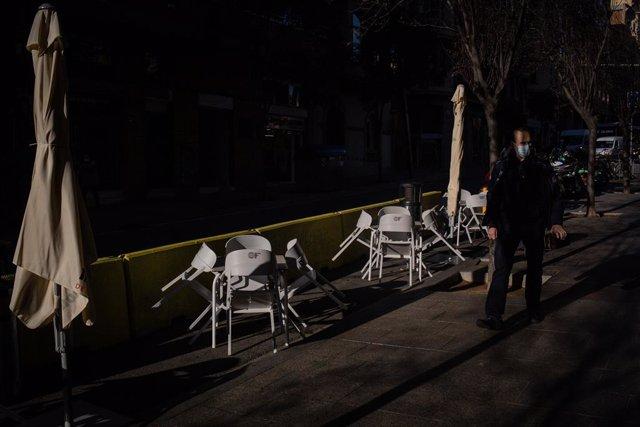 Un hombre pasa al lado de las sillas vacías de una terraza en Barcelona, Catalunya (España).