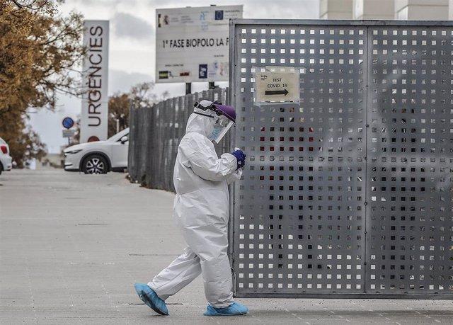 Un sanitario a los alrededores de la fila de vehículos para realizarse una prueba PCR de detección del coronavirus a las puertas del Hospital de Campaña próximo al de La Fe, en Valencia.
