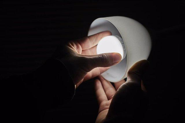 Un hombre cambia la bombilla de una lámpara