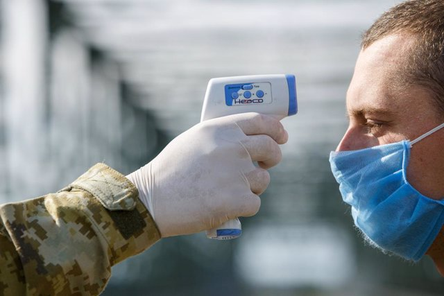 20 May 2020, Ukraine, Chop: A border guard personnel measures a man's body temperature at the Tysa international automobile checkpoint on the Ukraine-Hungary border during the coronavirus quarantine. Photo: -/Ukrinform/dpa