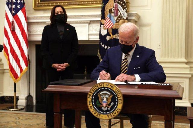 El presidente de Estados Unidos, Joe Biden, firma una orden ejecutiva ante la mirada de la vicepresidenta, Kamala Harris.