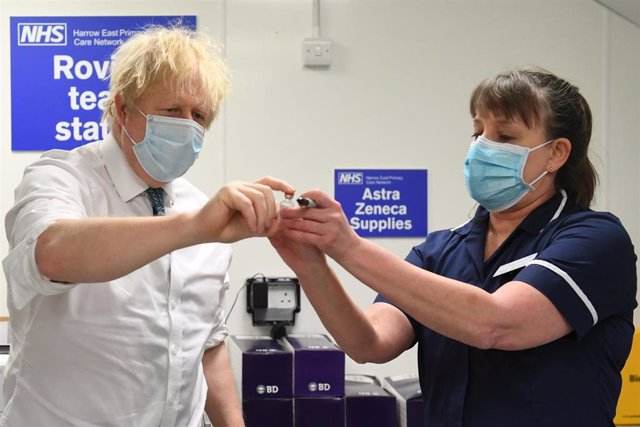 25 January 2021, United Kingdom, London: UK Prime Minister Boris Johnson (L) is shown a vial of the Oxford/Astrazeneca COVID-19 vaccine during a visit to Barnet FC's ground at The Hive, which is being used as a coronavirus vaccination centre.