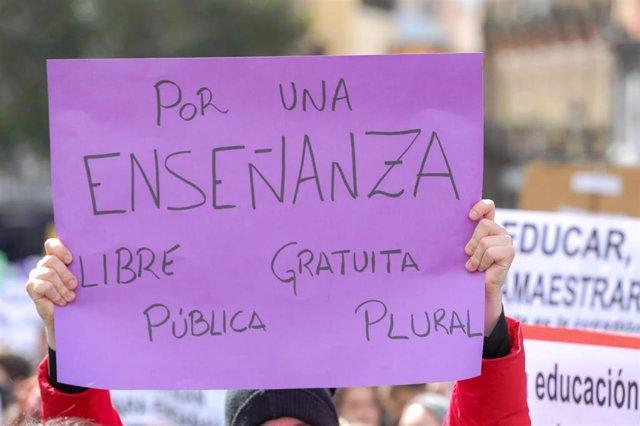 """Jóvenes con pancartas en las que se pueden leer """"Por una enseñanza libre, gratuita, pública y plural""""."""