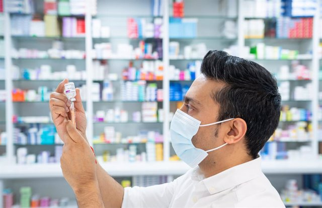 28 January 2021, United Kingdom, London: Pharmacist Bhaveen Patel draws up a dose of the Oxford/AstraZeneca COVID-19 vaccine in preparation for coronavirus vaccinations during a clinic held at Junction Pharmacy. The roll out of the vaccination programme c