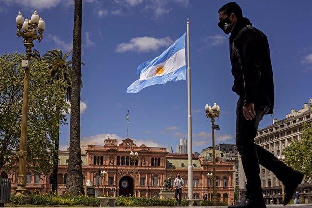 Un hombre con mascarilla pasea frente a la Casa Rosada.