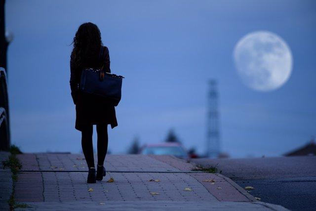 Mujer con la luna de fondo. Pasear a media tarde.