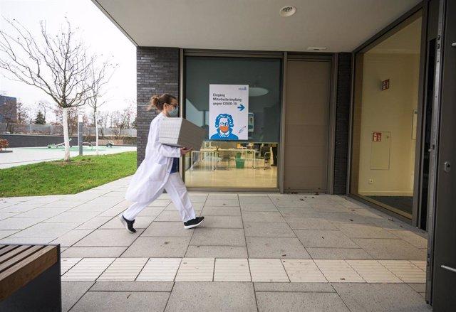 Una trabajadora sanitaria transporta una caja con vacunas contra el coronavirus en Alemania