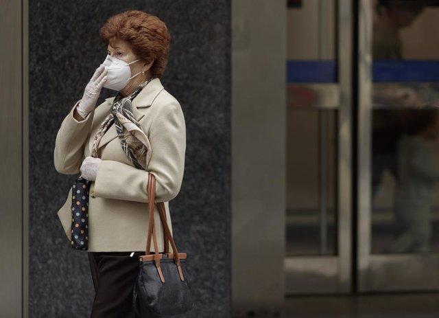 Una mujer camina con una mascarilla por la capital donde desde este pasado lunes las 2.882 farmacias madrileñas han entregado de forma gratuita siete millones de mascarillas FFP2 modelo KN95 entre la población de la Comunidad de Madrid (Foto de archivo).