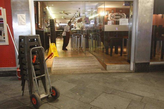 Un camarero recoge las mesas de la terraza de un bar en Palma.