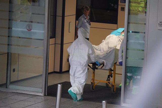 Un sanitario protegido con un traje y guantes de látex, empuja una camilla con una persona sobre ella en el Hospital Universitario Cruces