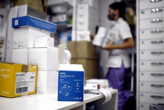 Vista de una de las cajas de test de antígenos para Covid-19 mientras una farmaceútica coloca varios productos en su farmacia.