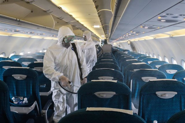 03 March 2020, Vietnam, Hanoi: Members of staff of the Center for Disease Control in Hanoi spray disinfectant inside a plane at Noi Bai International Airport amid the outbreak of Covid-19 (coronavirus). Vietnam Airlines on Monday agreed to stop all flight
