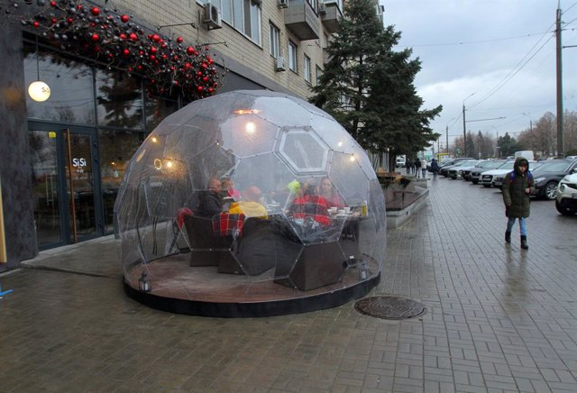 25 January 2021, Ukraine, Dnipro: People sit at the table under a glass cupola of a winter terrace opened in one of the city restaurants, Dnipro, east-central Ukraine. Photo: -/Ukrinform/dpa