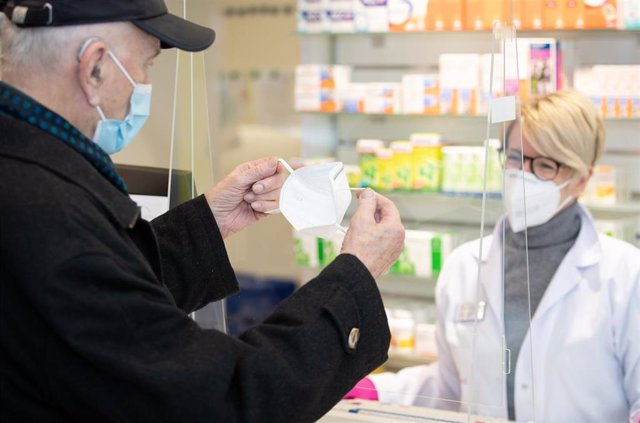 North Rhine-Westphalia, Bielefeld: An elderly man receives an FFP2 mask from Pharmacist Nadine Sallach.