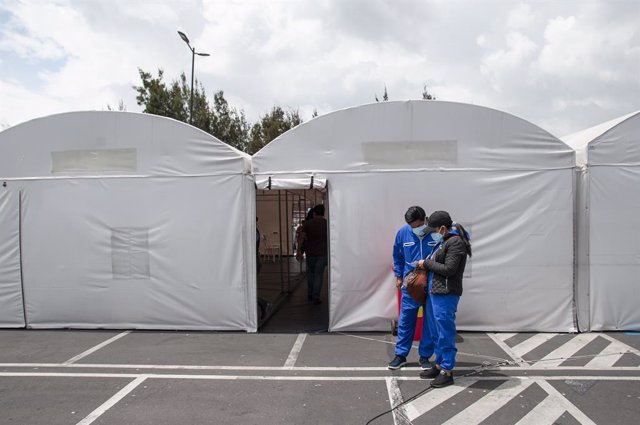 15 January 2021, Ecuador, Quito: Two patients check their PCR results outside the improvised tents in front of the Iess South Hospital were tested for the coronavirus. Photo: Juan Diego Montegro/