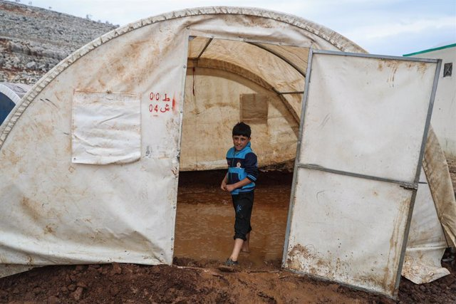 16 January 2021, Syria, Sarmada: A Syrian boy stands at the entrance of a tent flooded with rain water at the Baraem camp for internally displaced people. Photo: Anas Alkharboutli/dpa