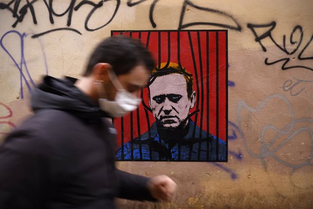 25 January 2021, Italy, Rome: A man wears a face mask as he passes past by a poster made by the street artist Harry Greb depicting the Russian opposition leader Alexei Navalny in the downtown of the city of Rome. Photo: Vincenzo Livieri/ZUMA Wire/dpa