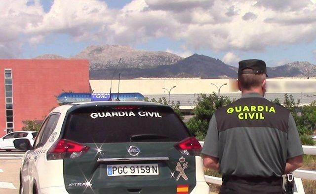 Un vehículo de la Guardia Civil y un agente de espaldas.