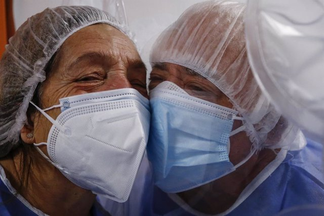 14 January 2021, Italy, Rome: A woman embraces her husband, who's infected with COVID-19, through the embrace tent at the New Castelli's Hospital which allows patients to have contact with family members during the COVID-19 hospitalization period. Photo: