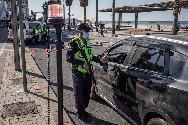 08 January 2021, Israel, Tel Aviv: Israeli police performs checks at a roadblock. Despite leading the global vaccination race Israel started it's third national lockdown in a bid to curb a sharp rise in new COVID-19 infections. Photo: Ilia Yefimovich/dpa
